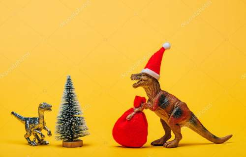 Toy dinosaurs with santa hat and sack beside pine on yellow background