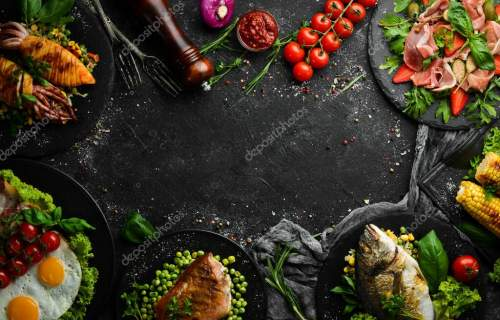 Food background. Set of dishes of fish, meat and vegetables on black stone background. Top view. Free copy space.