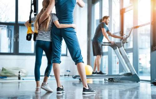 Woman with girl looking at handsome man workout on treadmill at gym