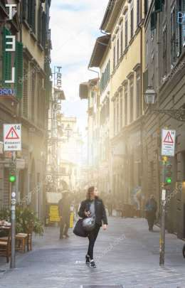 Tourists walk through the picturesque streets of Florence on a b