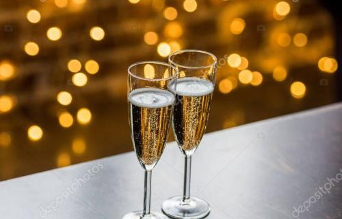 close-up view of two glasses of champagne and golden bokeh background
