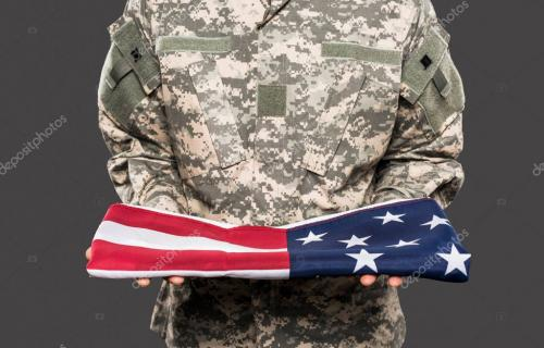cropped view of soldier in camouflage uniform holding american flag isolated on grey