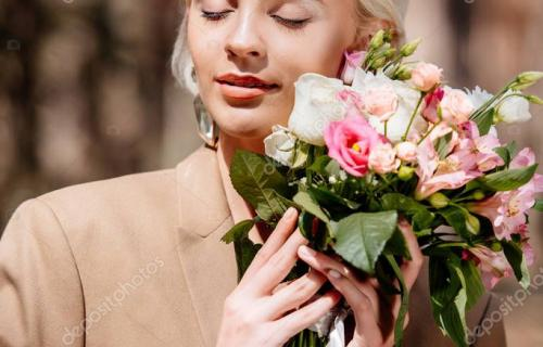 elegant young woman in brown jacket holding bouquet with closed eyes in forest