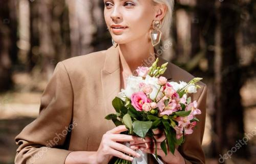 elegant blonde woman in earrings holding bouquet and looking away in forest