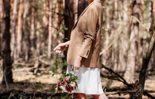 full length view of stylish bride holding wedding bouquet in forest