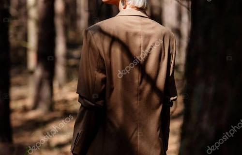 pensive blonde woman in brown jacket standing in forest