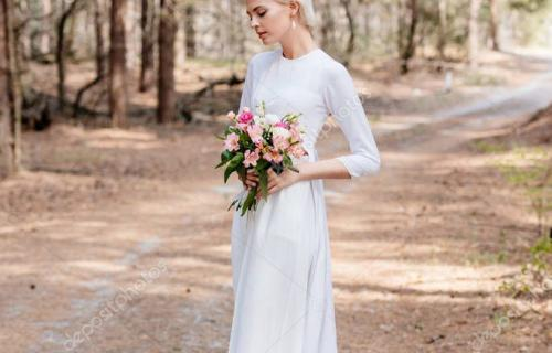 full length view of beautiful bride holding wedding bouquet in forest