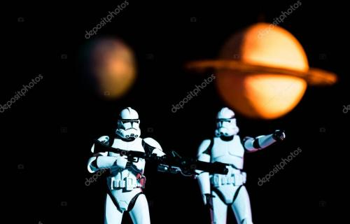 KYIV, UKRAINE - MAY 25, 2019: white imperial stormtroopers with guns and cosmic planets on background
