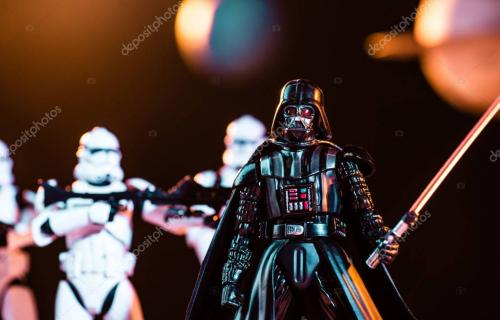 KYIV, UKRAINE - MAY 25, 2019: selective focus of Darth Vader with lightsaber and white imperial stormtroopers with guns on backg