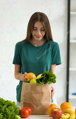 smiling young woman standing near paper bag with fresh vegetables and fruits at home