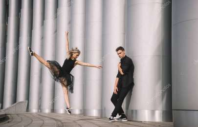 young couple of dancers in black clothes dancing near columns