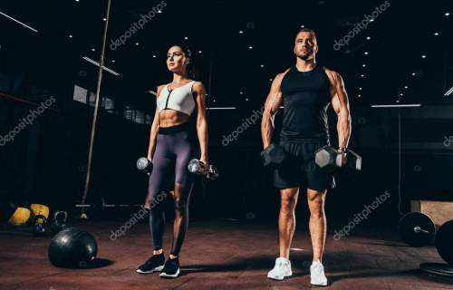 fit sportsman and sportswoman exercising with dumbbells together in dark gym