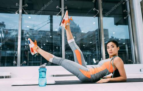 attractive asian girl lying with legs up on fitness mat at gym