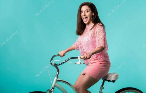 excited girl in pink outfit riding retro bike isolated on turquoise