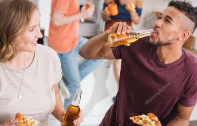 african american man drinking beer and holding pizza near multicultural friends