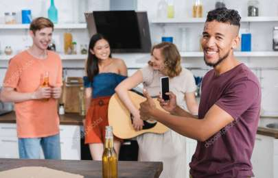 excited african american man showing thumb up while young woman playing guitar for multicultural friends