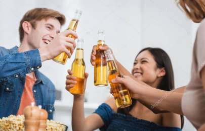 selective focus of multiethnic friends clinking bottles of beer during party