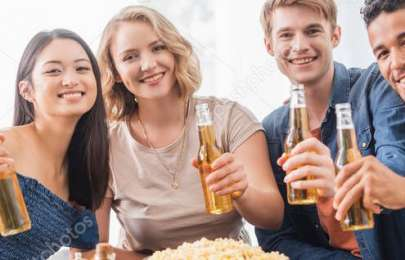 panoramic concept of joyful multiethnic friends looking at camera while holding bottles of beer
