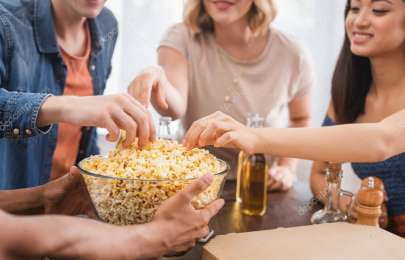 selective focus of multiethnic friends taking popcorn from bowl during party