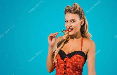 portrait of beautiful pin up woman in retro style clothing eating lollipop isolated on blue