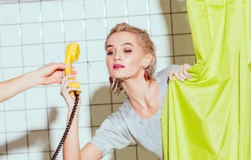beautiful woman taking yellow retro telephone handset in shower with green curtain