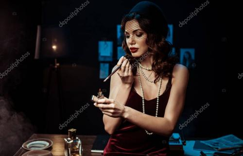 Beautiful woman with mouthpiece lighting cigarette with lighter in dark office