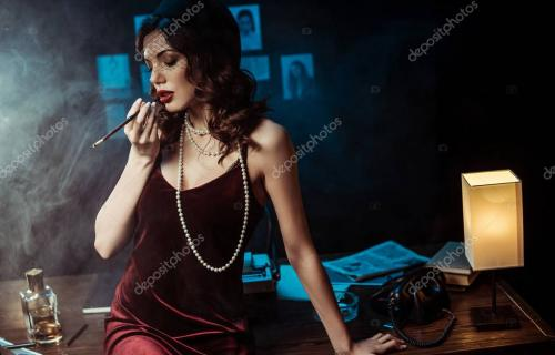 Woman in dress sitting on table and holding mouthpiece in dark office