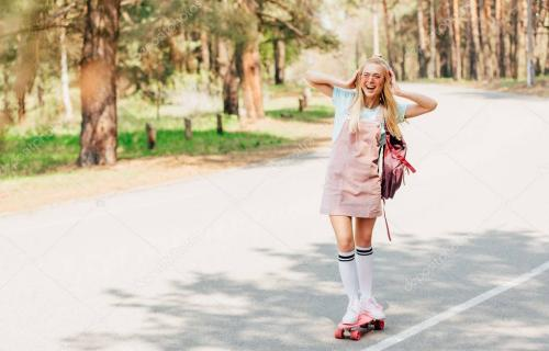 full length view of excited blonde girl skateboarding and listening music in headphones