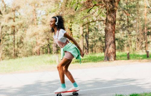 full length view of african american girl skateboarding and listening music in headphones