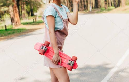 full length view of smiling blonde girl standing on road with penny board and waving hand