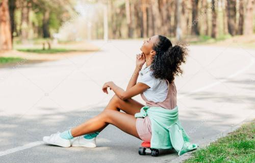 smiling african american girl with headphones sitting on penny board on road