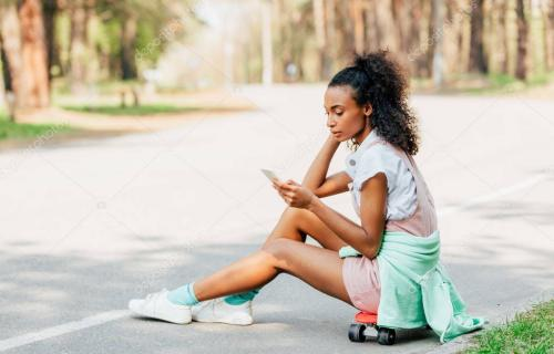 african american girl using smartphone while sitting on skateboard on road
