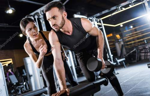 attractive trainer talking with bearded man working out with dumbbell