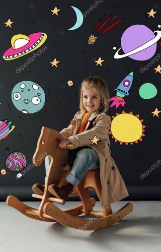 happy child in trench coat and jeans sitting on rocking horse on black background with fairy cosmic illustration