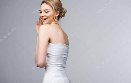 positive woman in wedding dress laughing isolated on grey