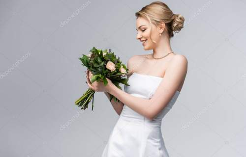 young and happy bride in white dress looking at bouquet of flowers isolated on grey
