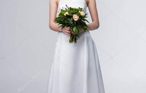 smiling girl in white wedding dress holding bouquet of flowers on grey