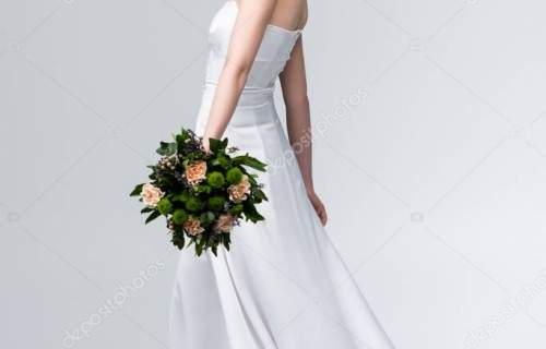 attractive bride in elegant wedding dress holding bouquet of flowers and smiling on grey