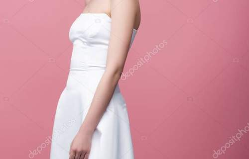 serious bride in white wedding dress looking at camera isolated on pink