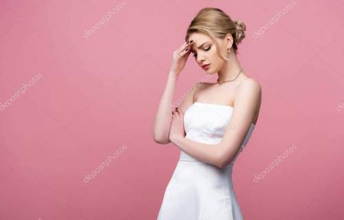 upset bride in white wedding dress touching forehead isolated on pink