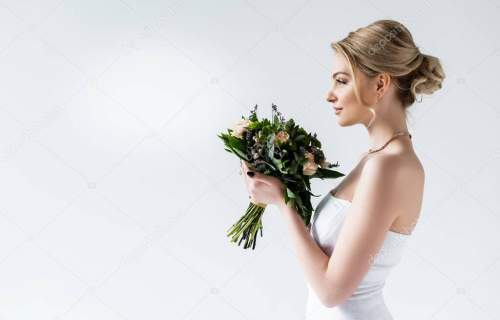 side view of attractive bride holding wedding flowers on white