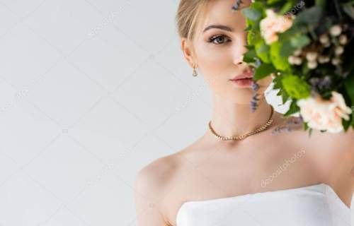 beautiful bride in elegant wedding dress covering face with flowers isolated on white