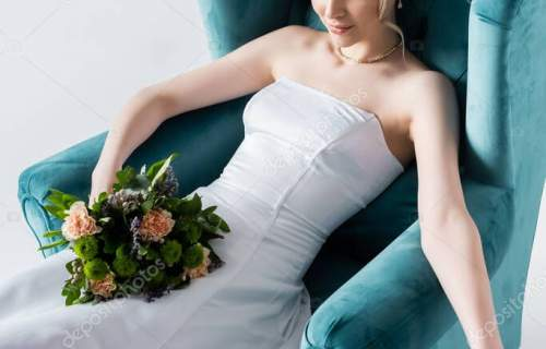 beautiful bride in elegant wedding dress holding flowers while sitting in armchair on white