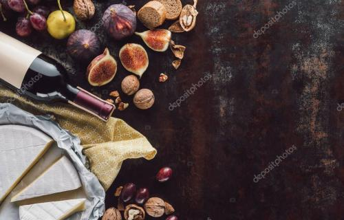 food composition with cheese, bottle of wine and fruits on dark tabletop