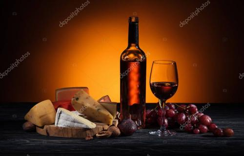 different types of cheeses, wine bottle and grapes on table on orange
