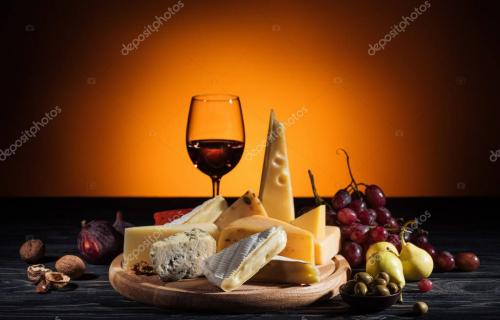 different types of cheeses, wineglass and fruits on table on orange