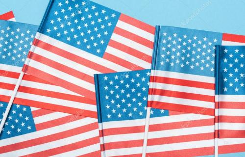 close up view of decorative american flags on sticks on blue background