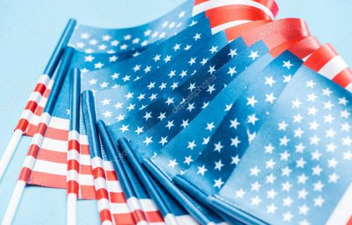 close up view of silk national usa flags on sticks on blue background