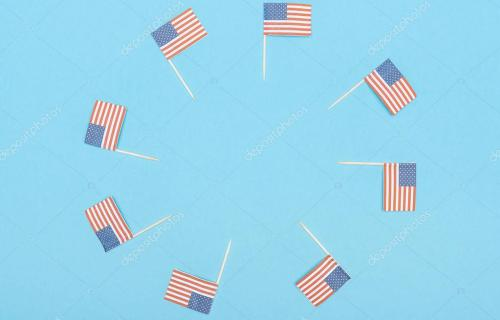 round frame made of paper cut decorative american flags on wooden sticks on blue background with copy space