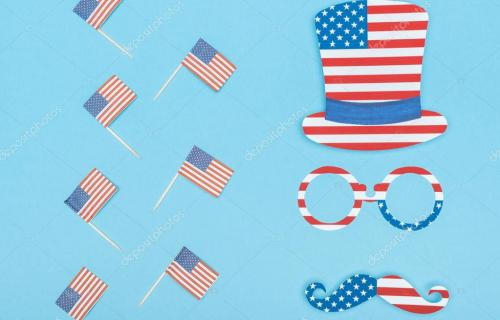 flat lay with hat, glasses and mustache made of stars and stripes near decorative american flags on wooden sticks on blue backgr